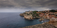 Photograph of the ocean port of Dubrovnik which is a walled city located within the southern part of Croatia and is situated along the Adriatic Sea. <br /> Built in the 16th century, It is known for its distinctive Old Town charm that has been encircled with massive stone walls to protect the city. <br /> Within the city walls are the St. Blaise Church, the Renaissance Sponza Palace, and the Gothic Rector's Palace which is now a history museum. Also located within the city are many small shops and restaurants.
