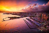 An aerial view of Magic Island and Ala Moana Beach during a colorful sunset on O'ahu, with the Ala Wai Yacht Harbor in the foreground.