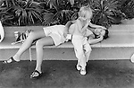 Mother and young child exhausted and tired lying on a bench Los Angeles California USA 1969 .