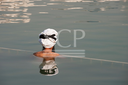 Amritsar, Punjab, India.  The Golden Temple - Harmandir Sahib - a Sikh man bathing in the holy water of the Amrit Sarovar wearing a white turban with his dagger tied round his head.