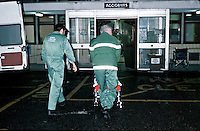 Paramedic ambulance crew taking a patient in a wheelchair into a hospital.