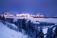 749451002 the rising sun breaks through winter storm clouds and highlights the snow covered teton range and fir trees surrounding the snake river seen from the snake river overlook in grand tetons national park wyoming