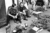 Two men with a collection of worthless bric-a-brac at a Krakow market.
