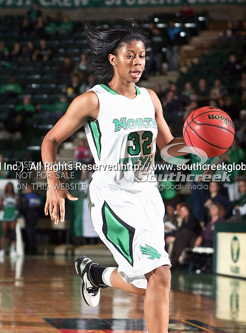 North Texas Mean Green guard Denetra Kellum (32) dribbles down court in the NCAA Womens basketball game between the Florida International University Panthers and the University of North Texas Mean Green at the North Texas Coliseum,the Super Pit, in Denton, Texas. UNT defeated FIU 76 to 69