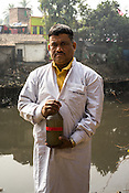 50 year old Ratan Routh, a laboratory assistant from the Institute of Serology poses with a bottle of collected sewage samples in Kolkata, West Bengal, India.