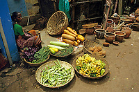 Woman selling baskets of fruit at a street market in Panjim, Goa, India.