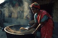 INDIA Karnataka, farm near Mangalore, woman boil paddy before peeling / INDIEN, Farm bei Mangalore, Frau kocht Reis vor dem Schaelen
