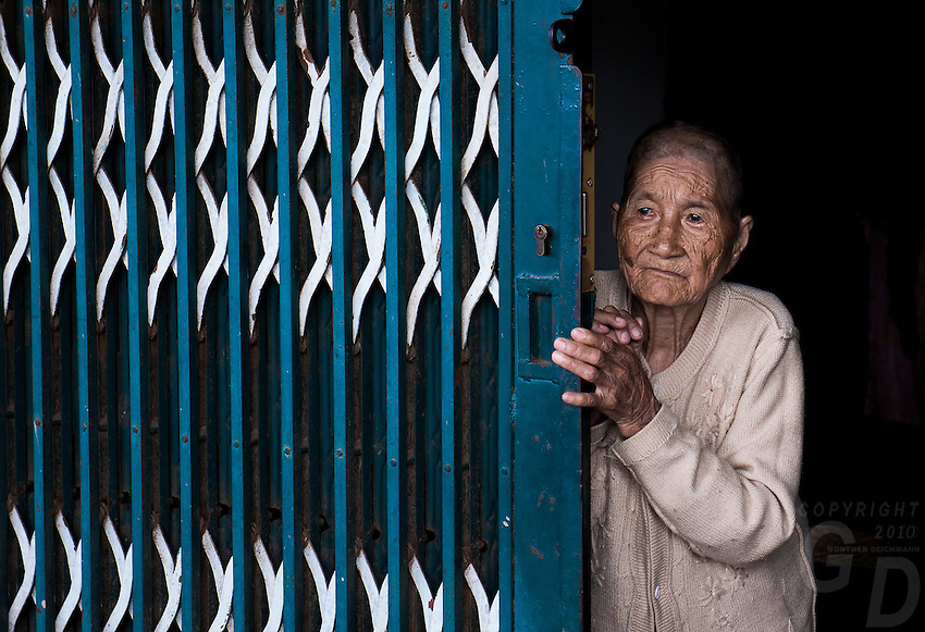 """This beautiful old lady just open the gate for me. Near Can Tho, the hub of the Mekong Delta (Vietnamese: Đồng bằng Sông Cửu Long """"Nine Dragon river delta""""), also known as the Western Region (Vietnamese: Miền Tây or the South-western region (Vietnamese: Tây Nam Bộ) is the region in southwestern Vietnam where the Mekong River approaches and empties into the sea through a network of distributaries. The Mekong delta region encompasses a large portion of southwestern Vietnam of 39,000 square kilometres (15,000 sq mi). The size of the area covered by water depends on the season.<br /> The Mekong Delta has been dubbed as a """"biological treasure trove"""". Over 1,000 animal species were recorded between 1997 and 2007 and new species of plants, fish, lizards, and mammals has been discovered in previously unexplored areas, including the Laotian rock rat, thought to be extinct."""