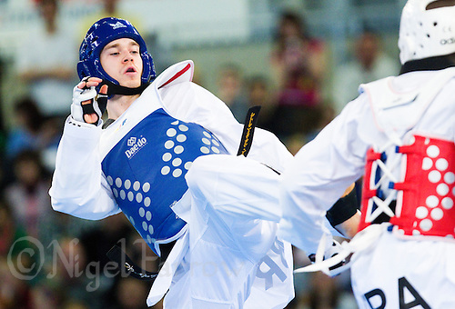 05 MAY 2012 - MANCHESTER, GBR - Aaron Cook (GBR) of Great Britain (left) aims a kick at Ynoussa Sawadogo of France during their men's 2012 European Taekwondo Championships -80kg category second round match at Sportcity in Manchester, Great Britain .(PHOTO (C) 2012 NIGEL FARROW)