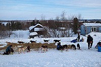 Ray Redington Jr. leaves the Shageluk checkpoint as veterinarians check out Ed Stielstra 's dogs during Iditarod 2009