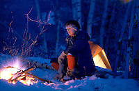 A woman camps in winter snow near a blazing fire.