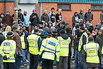 © Joel Goodman - 07973 332324 . 25/02/2012 . Hyde , UK . Police and community mediators stand with a group of Asian men near to the demonstration . The EDL demonstrate following an assault on Daniel Stringer-Prince, whose family say they do not want the demonstration to take place in the town in their son's name. The EDL say Daniel was assaulted by a gang of Asian men . At the same time , the BNP hold a rally in the town . Photo credit : Joel Goodman