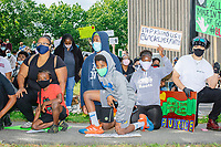 """People take a knee for 8 minutes and 46 seconds outside the Boston Police Department Headquarters during the """"Peaceful Children's March: Be the Change"""" demonstration in support of Black Lives Matter in Boston, Massachusetts, on Sun., June 7, 2020. The children's march was organized by siblings Naheem, 7, and Anaysha Benalfew, 10. The demonstration is part of a weeks-long nationwide response to the killing of George Floyd by Minneapolis police on May 25, 2020. The march started near the Nubian Square bus depot and continued to the nearby Boston Police Department headquarters, where marchers knelt for 8 minutes and 46 seconds, the time that police officers knelt on George Floyd's neck during his killing. A number of children, mostly people of color, then spoke about how people should be treated equally and how they wished they didn't have to grow up fearful that a police officer would kill them or their loved ones.  The signs here read """"Stop Killing Us"""" and """"Black Lives Matter."""""""