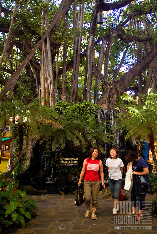 Tourists walk by lush foliage at the International Market Place in Waikiki.