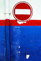 'One Way' street sign on a red, white and blue painted wall, Malé, Maldives.