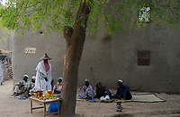 MALI, Djenne, muslim men sitting infront of clay building