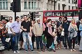 Pedestrians walking to the Hyde Park London 2012 Olympic Games Live Site wait at a road crossing at Marble Arch