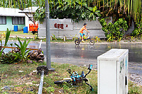 A young boy rides his bicycle though the Tuvaluan capital of Funafuti. Located in the South West Pacific Ocean, Tuvalu is the world's 4th smallest country and is one of the most vulnerable to climate change impacts including sea level rise, drought and extreme weather events. Tuvalu - March, 2019.