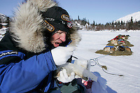 March 5, 2007   Rainy Pass checkpoint----   Hans Gatt eats strogonoff from a plastic bag at the Rainy Pass checkpoint on Puntilla Lake with the Alaska Range in the background.