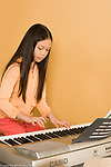 9 year old girl playing musical instrument piano keyboard