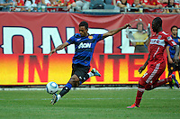 Manchester United midfielder Nani (17) shoots the ball while being pursued by Chicago Fire midfielder Patrick Nyarko (14).  Manchester United defeated the Chicago Fire 3-1 at Soldier Field in Chicago, IL on July 23, 2011.