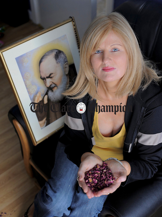 Anne Henry holds some rose petals from St. Padre Pio's grave. Photograph by John Kelly.