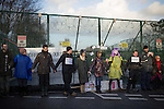 © Joel Goodman - 07973 332324 . 26/01/2014 . Salford , UK . Protesters link hands and stand in front of the gate leading to the fracking site . Protesters march to an iGas fracking exploration site at Barton Moss , Salford , today (Sunday 26th January 2014) . A long term protest camp has been established on an access road leading to the site and today (26th January) protesters from other areas of the country travelled to the site to join with other protesters against fracking . Photo credit : Joel Goodman