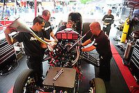 Aug. 5, 2011; Kent, WA, USA; Crew members work on the engine for the car of NHRA funny car driver Cruz Pedregon during qualifying for the Northwest Nationals at Pacific Raceways. Mandatory Credit: Mark J. Rebilas-