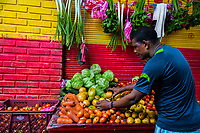 An Afro-Colombian market vendor sells fresh fruits and vegetables in the market of Bazurto in Cartagena, Colombia, 12 December 2017. Far from the touristy places in the walled city, a colorful, vibrant labyrinth of Cartagena's biggest open-air market sprawls to the Caribbean seashore. Here, in the dark and narrow alleys, full of scrappy stalls selling fruit, vegetables and herbs, meat and raw fish, with smelly garbage on the floor and loud reggaeton music in the air, the African roots of Colombia are manifested.