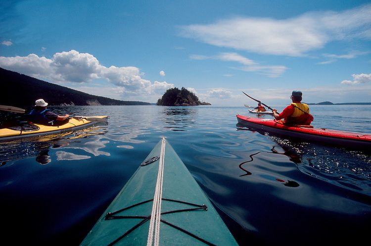 Sea kayakers, San Juan Islands,  paddliers the approaching Strawberry Island, Washington State, Pacific Northwest..