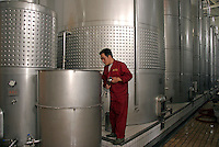 A worker operates a machinery at the fermentation room of Grace Vineyard in Taigu County, Shanxi Province, China. Established in an area that have been growing grapes since the Tang Dynasty (618-906 A.D.) with Hong Kong and French investment, the winery seeks to set itself apart from mass-produced mainstream Chinese wines with French expertise and smaller scaled production. With increased income and western influence, the number of Chinese wine drinkers has increased at an annual rate of 10% in the past ten years, 10 times of that of the world average of 1%..07 Jul 2005