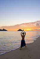 Silhouette of a slim woman with her arms over her head in a yoga pose with a beautiful sunrise  in the distance. Photographed at world famous Lanikai beach on the windward side of Oahu, with the Mokulua Islands on the horizon.