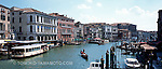 Panoramic photo/foto of the Grand Canal (Canal Grande) viewed from the Rialto Bridge.   This view of the canal includes the quayside, a vaporetto, a gondola in the middle of the canal, and a clear view of two palazzos, Palazzos Bembo and Manin-Dolfin against a blue stky with summery clouds. Travel photo of Venice, Italy by Tomoko Yamamoto. Original on 120 slide film taken with Mamiya 6 (Medium Format). High-resolution file of 100 MB:<br /> 8880x3804 pixels 96.6 Mb TIFF;29.6x12.7 inches or 75x32cm at 300 dpi color; <br /> 24 Mb JPEG<br /> <br /> Unsharpened file available. Contact the photographer for details.<br /> <br /> Panoramaaufnahme, Panoramabild im Mittelformat auf dem Canal Grande aus der Rialtobrücke in Venedig, Italien.  Venezia, Italia