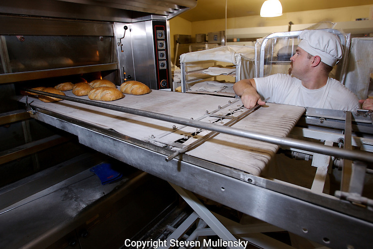 A baker checks the doneness of loaves.