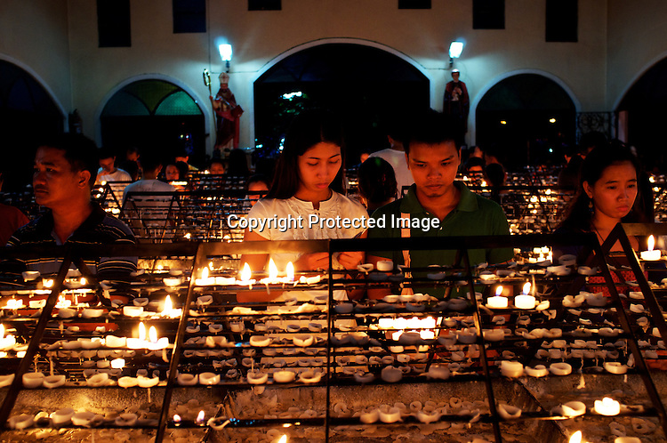 """Worshippers light candles to complement their prayers on wednesday evening at the Redemptorist Church in Baclaran in Manila, Philippines. The Baclaran church is said to be the most attended church in Asia drawing up to 100,000 worshippers """" in Manila, Philippines. Photo: Sanjit Das"""