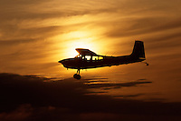 A small Cessna airplane flies through golden clouds at dawn.