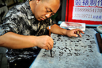 An artist practicing calligraphy with ink and water. Dafen is home to an art industry producing replicas, as well as original works, of pieces by the world's great artists for sale overseas. The success of this business has attracted more and more trained artists to the town seeking an opportunity to make a living.