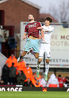 Sunday 07 December 2014<br /> Pictured L-R: Andy Carroll of West Ham battling for a header against Ki Sung Yueng of Swansea<br /> Re: Premier League West Ham United v Swansea City FC at Boleyn Ground, London, UK.