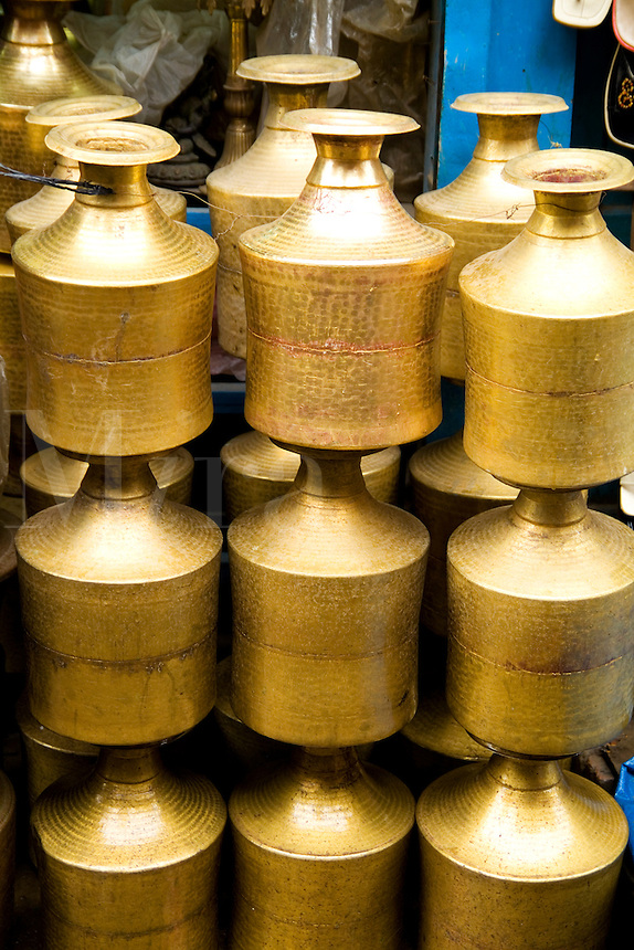 Stack of brass milk jugs in Durbar Square in center of village of Kathmandu, Nepal