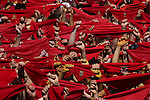 Participants hold red scarves as they celebrate the 'Chupinazo' marking the start at noon sharp of the San Fermin Festival at Castle square in Pamplona, northern Spain on July 6, 2013. Ten of thousands of people packed Pamplona's streets for a drunken kick-off to Spain's best-known fiesta: the nine-day San Fermin bull-running festival. © Pedro ARMESTRE
