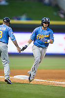 Ben Carhart (22) of the Myrtle Beach Pelicans slaps hands with Myrtle Beach Pelicans manager Mark Johnson (8) as he rounds third base after hitting a home run against the Winston-Salem Dash at BB&T Ballpark on April 18, 2015 in Winston-Salem, North Carolina.  The Pelicans defeated the Dash 8-4 in game two of a double-header.  (Brian Westerholt/Four Seam Images)