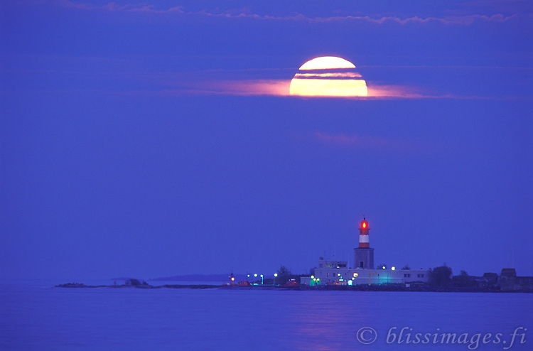 A full moon dramatically breaks through the clouds over Harmaja lighthouse in the Gulf of Finland just to the south of Helsinki