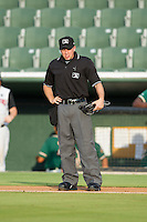 Home plate umpire Darin Tyson between innings of the South Atlantic League game between the Greensboro Grasshoppers and the Kannapolis Intimidators at CMC-Northeast Stadium on June 12, 2014 in Kannapolis, North Carolina.  The Grasshoppers defeated the Intimidators 5-2.  (Brian Westerholt/Four Seam Images)