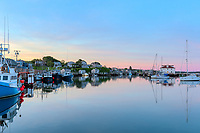 The commercial fishing village of Menemsha and boats docked in Menemsha Basin under a colorful sky during morning twilight, in Chilmark, Massachusetts on Martha's Vineyard.