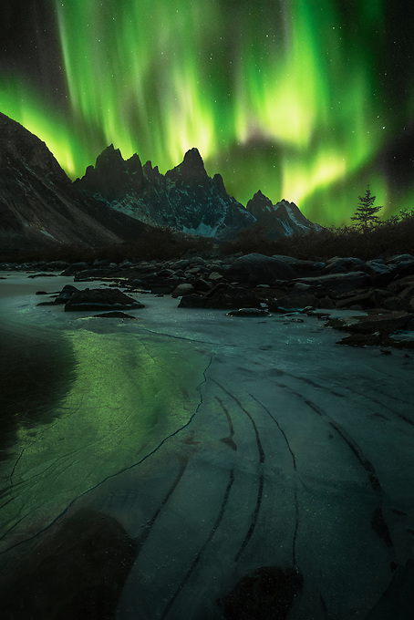 Tombstone Mountain framed under the northern lights, reflected in the ice and snow on a frozen lake below.