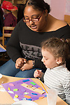 Education preschool childcare 3-4 year olds female teacher talking with girl, looking at collage she made with wood and colorful shapes
