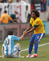Brazil defender Marcelo (6) helps Argentina forward  Lionel Messi (10) to his feet. In an international friendly (Clash of Titans), Argentina defeated Brazil, 4-3, at MetLife Stadium on June 9, 2012.