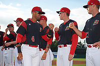 Batavia Muckdogs second baseman J.C. Millan (4) greets teammates Hunter Wells (35) and Brent Wheatley (23) during introductions before a game against the Auburn Doubledays on June 19, 2017 at Dwyer Stadium in Batavia, New York.  Batavia defeated Auburn 8-2 in both teams opening game of the season.  (Mike Janes/Four Seam Images)