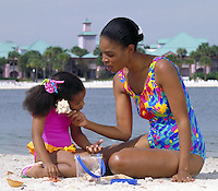 AFRICAN-AMERICAN MOTHER AND DAUGHTER SITTING TOGETHER ON BEACH AND LISTENING TO A SHELL. AFRICAN AMERICAN MOTHER AND DAUGHTER. ORLANDO FLORIDA.