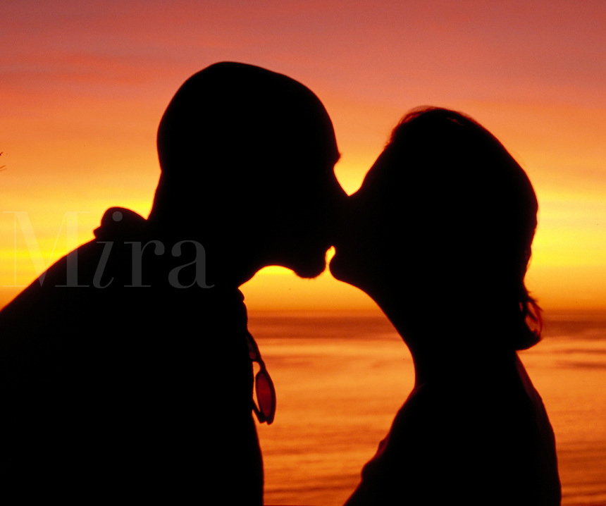 Silhouette of a kissing couple by the sea, sunset, couples, romance, romantic setting, love. Couple. California.